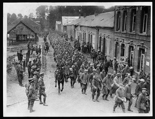Captives marching through a town, during World War I. Prisoners taken captive by Canadian soldiers march through a small town. Soldiers and civilians watch from the roadside, as the captives are escorted through town by men on horseback. An image such as this would make good propaganda, and may have appeared in British or Canadian newspapers. It offers evidence that the Allies are making progress and beating down the enemy.