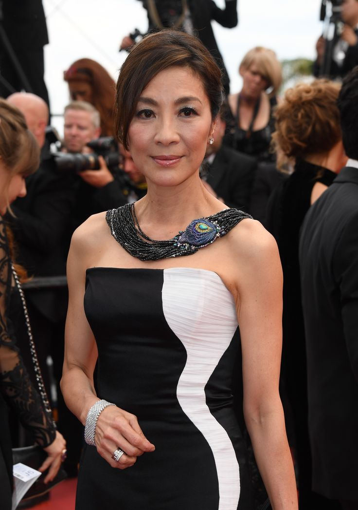 Dressed in an elegant black and white Gyunel gown, Chinese Malaysian Actress Michelle Yeoh wore a necklace from Chopard's 2017 Red Carpet Collection, in 18 carat white gold and titanium featuring a black opal, spinels, sapphires, diamonds, opals, tsavorites and amethysts. For glamour celebrity fashion Cannes Film Festival red carpet jewellery spotting travel here: http://www.thejewelleryeditor.com/jewellery/top-5/cannes-film-festival-red-carpet-jewellery-day-two/ #jewelry