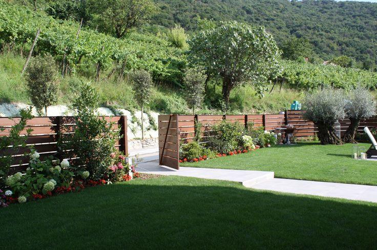 Giardino con staccionata in carpenteria metallica a disegno effetto corten - villa a Paratico - Manto erboso di essenze arboree e arbustive delle specie locali e presenti nel contesto