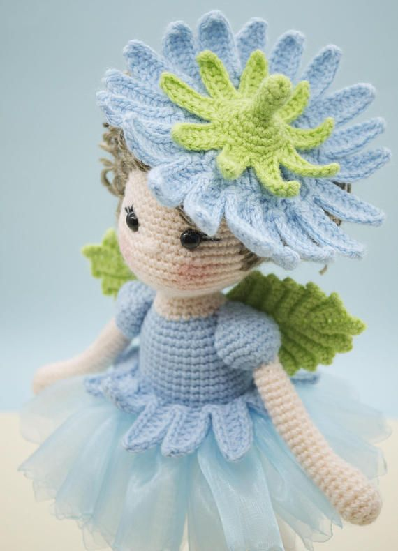 This is a finished handmade amigurumi crochet doll of a sweet Chicory flower fairy. She wears a beautiful blue organza skirt topped with crochet petals made to look like a Chicory flower. On her back are little green leaf wings and on her head of curls is a removable floral hat. Her shoes were made to match her outfit and have two little crochet leaves on each shoe for embellishment This Chicory flower fairy was lovingly handmade with the following materials: - 100% acrylic yarn - 100%…