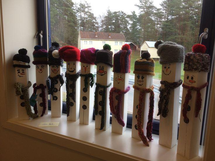 Pusset og malt snømann, strikket lue, selvlaget dusk og fingerheklet skjerf.