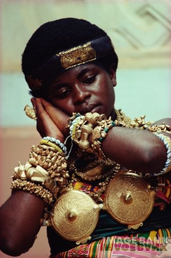 Africa | Asante Ceremonial jewellery.  This image appears in the Worldwide History of Beads publication together with the following comment ' A young Ashante court dancer performs the Adowa, a traditional dance, for the royal assembly.  She is adorned with gold belonging to the royal treasury, including bracelets made with hollow cast gold beads and old glass beads, some of which are valued more than gold.  Kumasi, Ghana. 1995.'