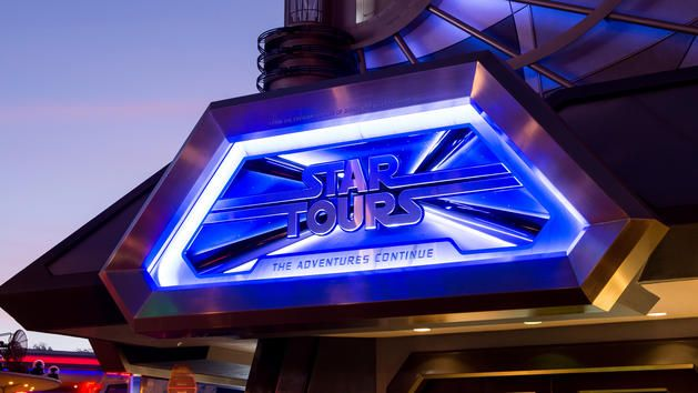 As night falls, the illuminated entrance sign for Star Tours The Adventures Continue welcomes Guests
