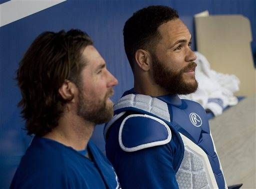 Toronto Blue Jays starting pitcher R.A. Dickey, left, talks with with catcher Russell Martin, right, during third-inning spring training baseball game action against the Baltimore Orioles in Dunedin, Fla., Friday, March 6, 2015.
