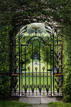 View through a decorative wrought-iron gate into the summer garden at Antony, Cornwall, England. An 18th century house which found fame in 2008 as the backdrop for the filming of The Mad Hatter's Tea Party in Disney's Alice in Wonderland