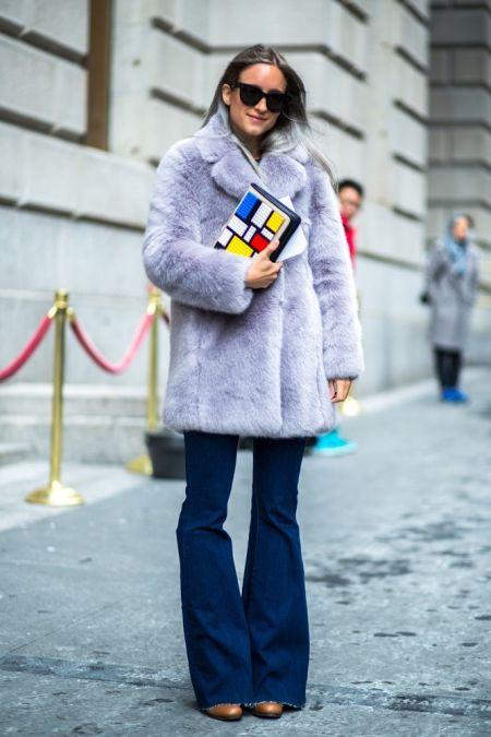 Dziewczyna w fioletowym futerku i jeansowych dzwonach, w dłoniach trzyma kolorową kopertówkę