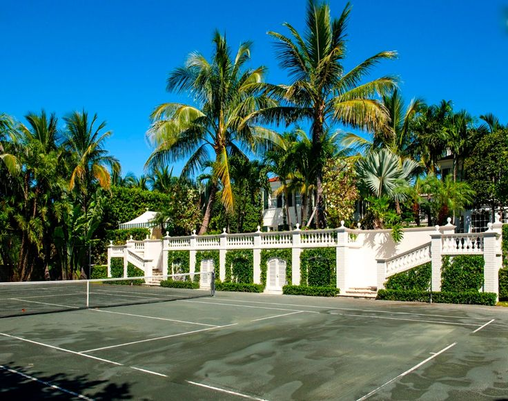 Sunken clay tennis court and pavilion on the side of a 1920s manse in Palm Beach. Are you peeping that green and white striped tent in the far-back? Yes, please.