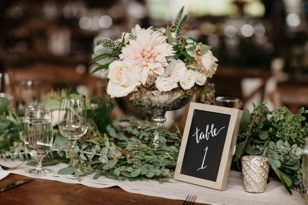 Lots of greenery, chalkboard table number, elegant centerpiece | Image by Jordan Voth