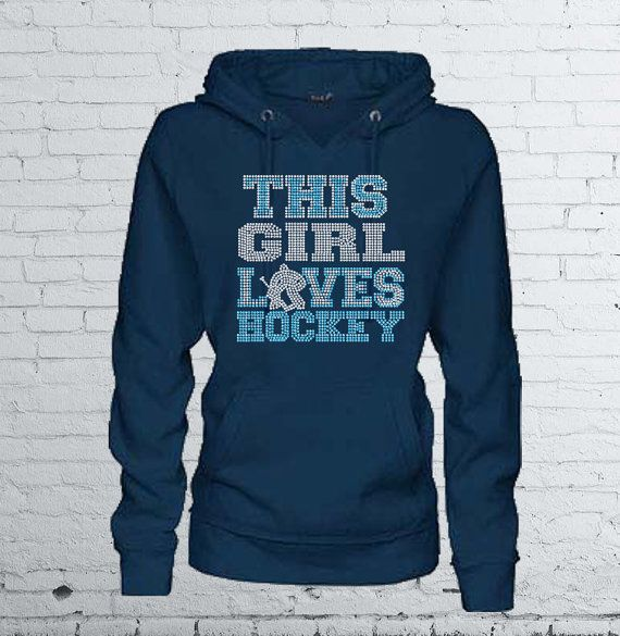 """This Girl Loves Hockey"" Women's Hoodie Sweatshirt by MadJoApparel. Embellished with premium rhinestone bling. Makes a great gift for a hockey mom or fan!"