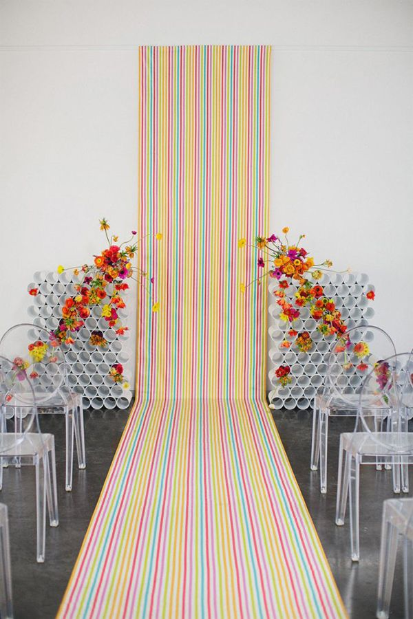Fabric Runner: If you find a bolt of fabric you like that matches your wedding theme, then buy yards and yards of it, and extend it from the back wall and down the length of the aisle. Here, they also stacked PVC tubes to create a modern display flanking the runner, which also served as vessels for matching floral arrangements