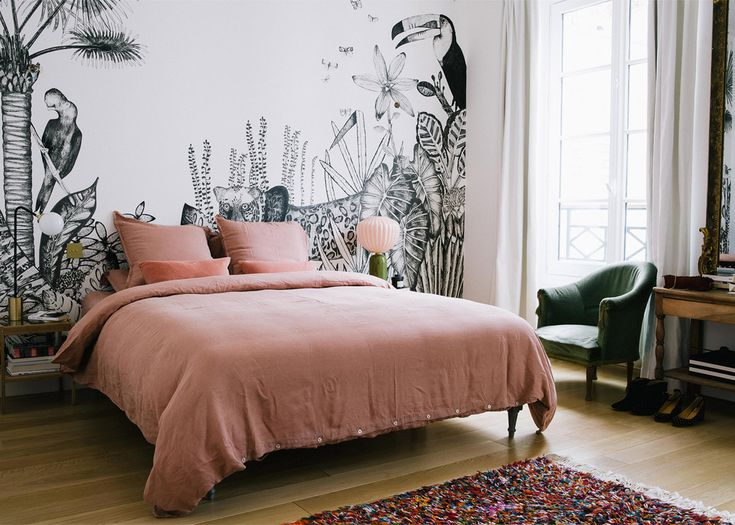 pink linen sheets and a black and white jungle mural in the bedroom | a happy chic parisian apartment tour via coco kelley