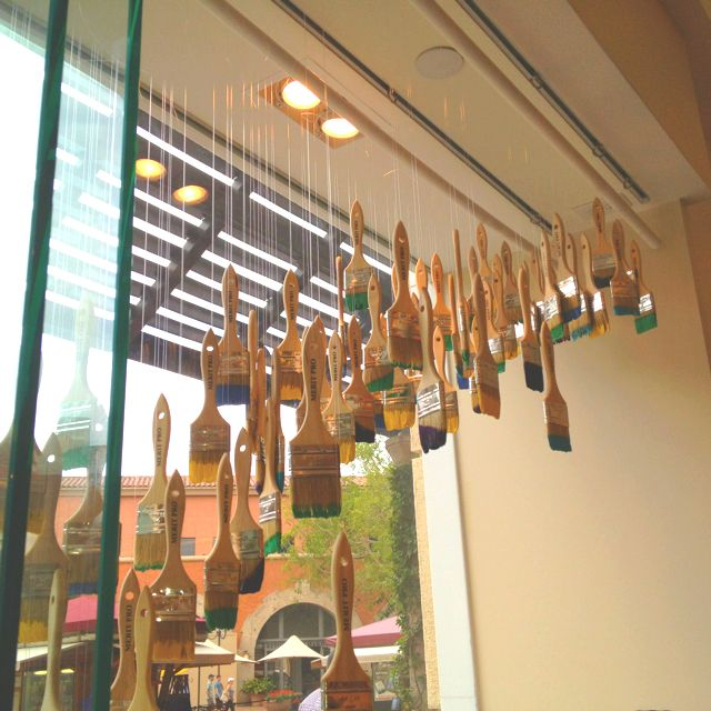 Hanging dipped paintbrushes as a window display/art installation at the Kate Spade store... Easy, cost effective, brilliant!