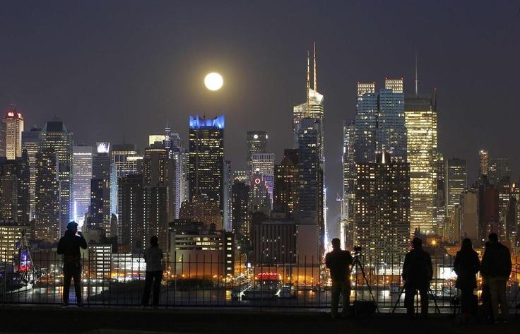 Personas fotografían la luna llena sobre Nueva York desde la orilla de New Jersey