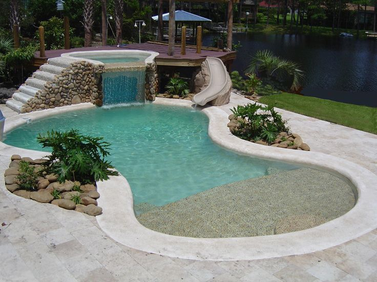 A landscape design of pool along with a small waterfall for Swimming pool waterfalls construction