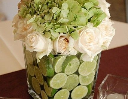 Centro de mesa con hortensias verdes, rosas blancas y limones partidos