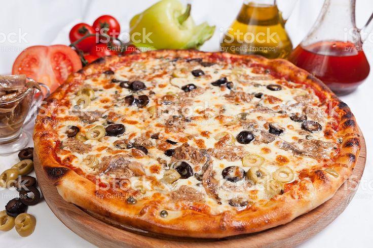 """Пицца """"Маринара""""      тесто для пиццы     томатный соус     200 г замороженного коктейля из морепродуктов, разморозить     1 ст. л. каперсов     1 желтый сладкий перец     1 ст. л. порезанного свежего майорана     1/2 ст. л. сухого орегано     60 г сыра Моццарелла, тертого     15 г Пармезана, тертого     12 черных оливок     оливковое масло     соль и перец     для украшения майоран или орегано"""