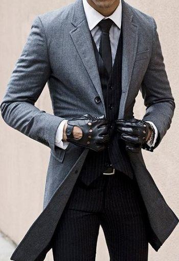 Den Look kaufen: https://lookastic.de/herrenmode/wie-kombinieren/mantel-weste-businesshemd-anzughose-krawatte-guertel-handschuhe/5338 — Weißes Businesshemd — Schwarze Krawatte — Schwarze vertikal gestreifte Anzughose — Dunkelbrauner Ledergürtel — Dunkelbraune Lederhandschuhe — Schwarze vertikal gestreifte Weste — Grauer Mantel