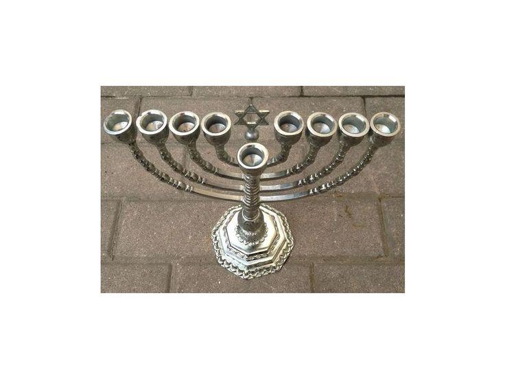 Bílý židovský devítiramenný stabilní chanukový svícen má sestupný schoďovitý vlnovatý osmiboký podstavec.