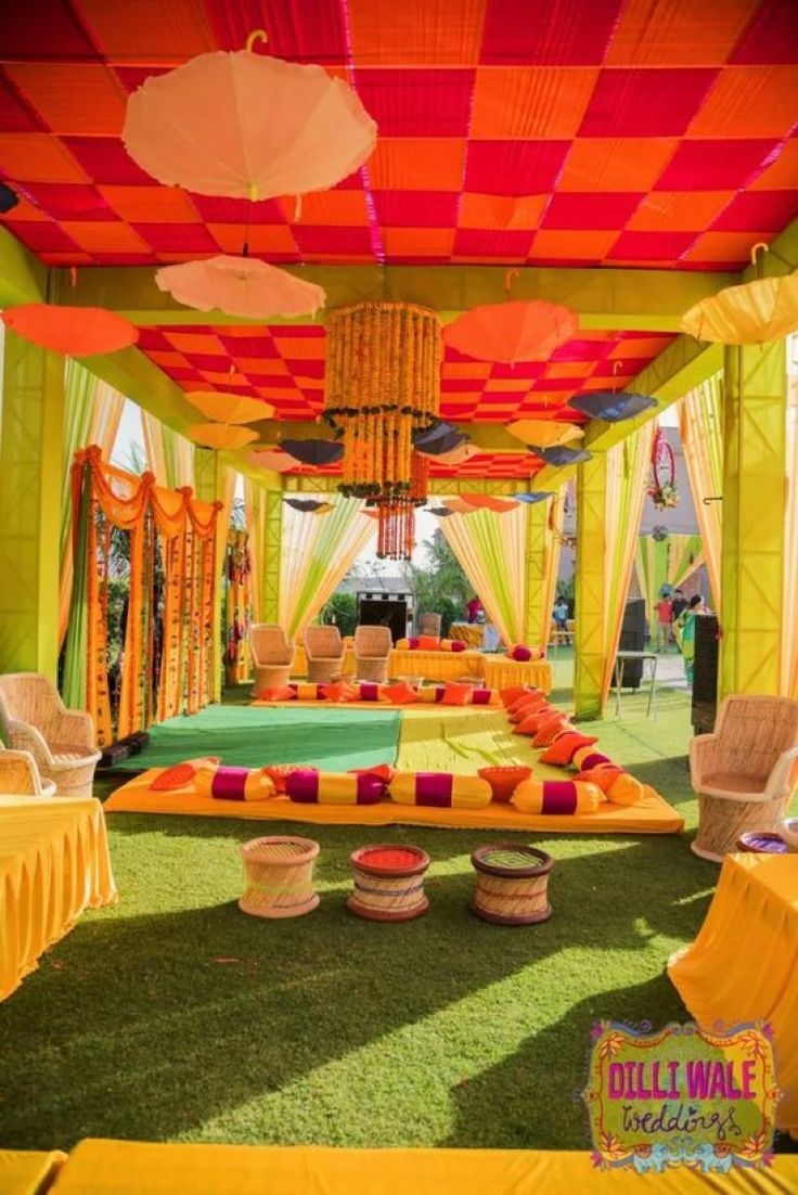 Checkered red and orange roof pattern with green pillars and peach umbrella decorations | love the quirky seating arrangements | outdoor mehendi ideas | Quirky Indian Tent Wedding | Credits: Dilli Wale Weddings | Every Indian bride's Fav. Wedding E-magazine to read. Here for any marriage advice you need | www.wittyvows.com shares things no one tells brides, covers real weddings, ideas, inspirations, design trends and the right vendors, candid photographers etc.