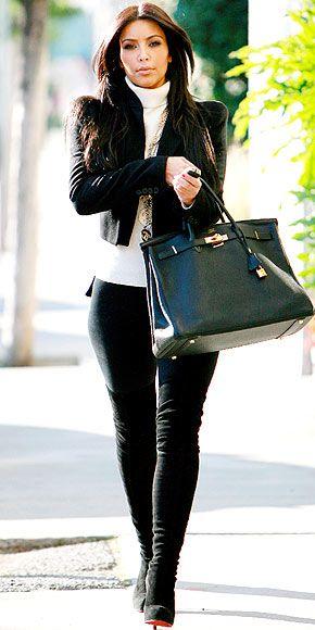Kim Kardashian in a chic cream turtleneck, cropped blazer and layered chains.