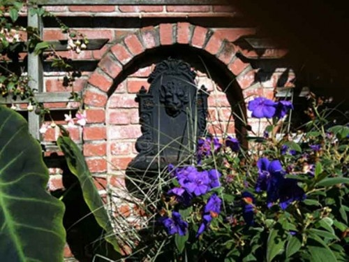 A tiny fountain set into a chimney enlivens a niche near a frequently-used door. The purple blooms are a Tibouchin.