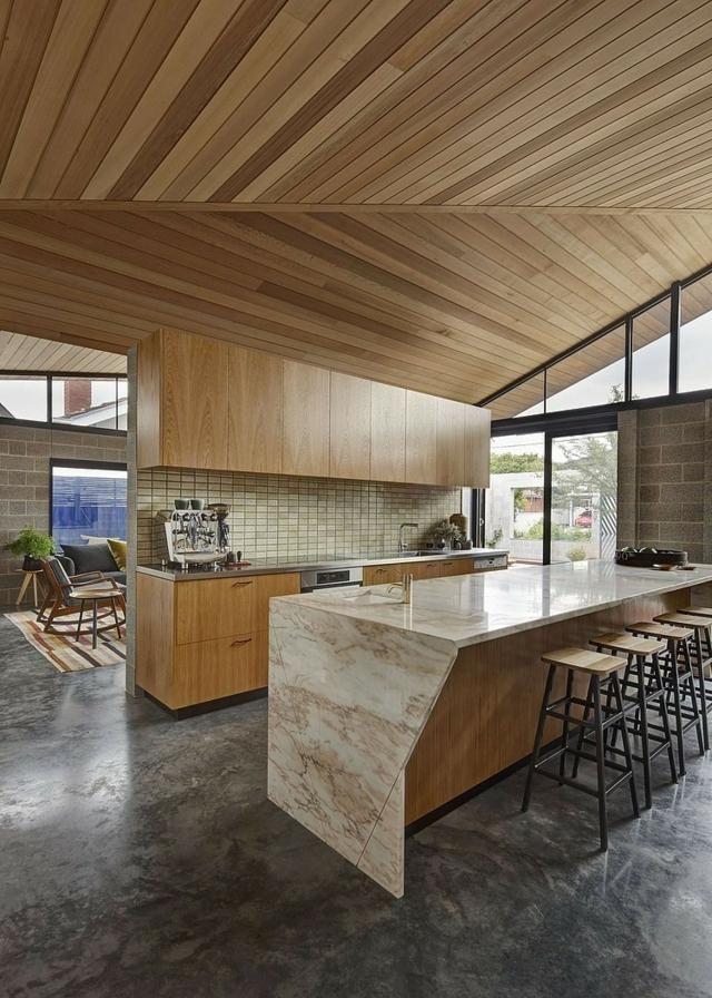 une cuisinette en bois avec un dessus d'îlot en marbre