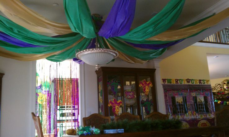 Inexpensive colorful plastic tablecloths draped across ceiling for Mardi Gras party