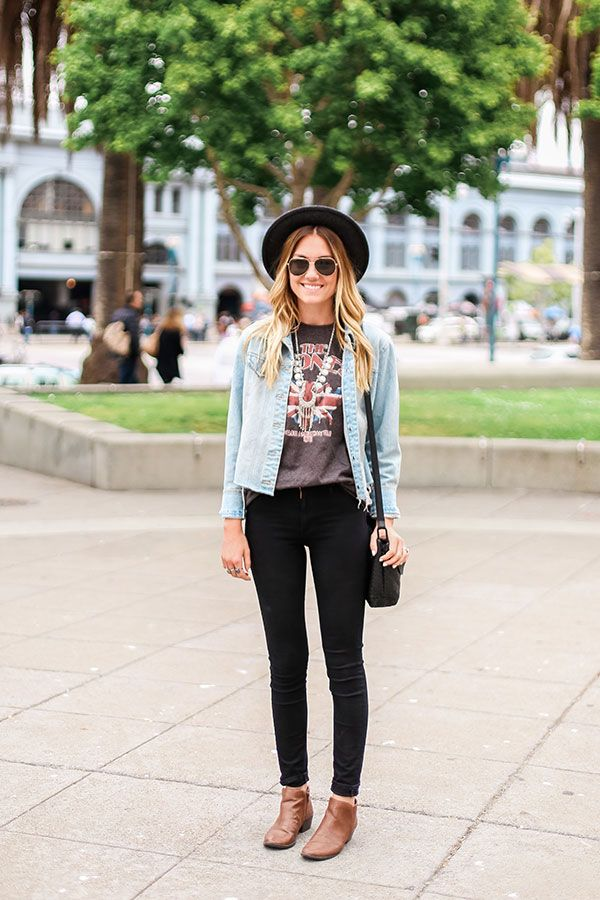 Thrifty festival look with the black brimmed hat, round sunglasses, denim jacket, graphic tee, black jeans, and brown ankle boots