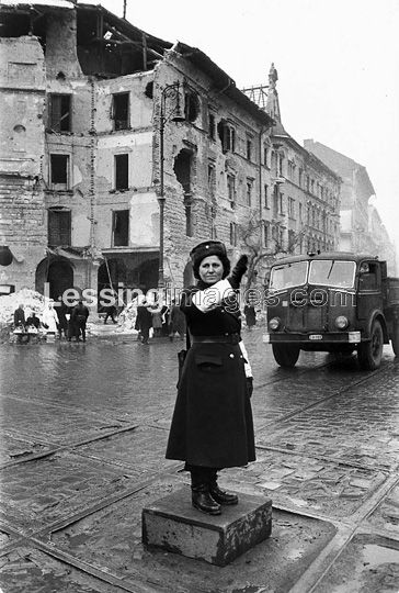 Aftermath of the Hungarian Revolution:a policewoman directs non-existing traffic at a Budapest crossing. Budapest,1956