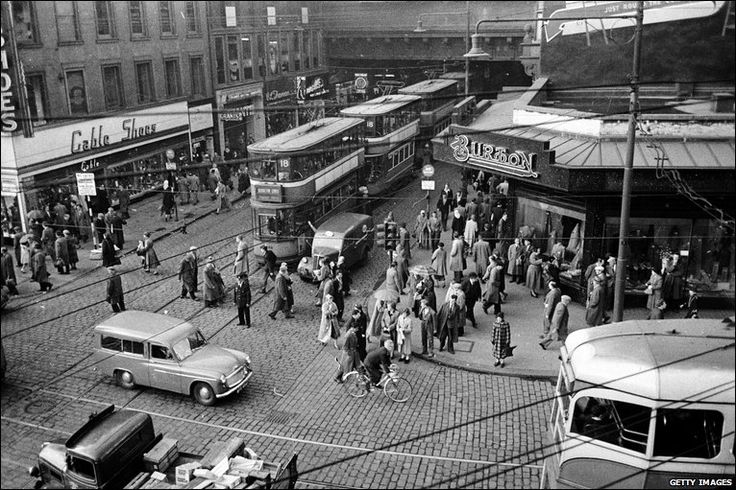 A line of trams emerges from the shelter of Heilanman's Umbrella in Glasgow, where Argyle Street passes under Central Station and dissects Union Street, 1955.