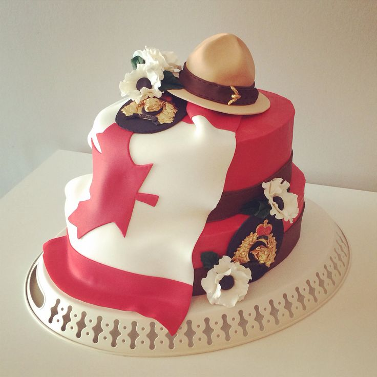 RCMP Cake. Red butter cream covering 2 oval cakes. With the Canadian flag in fondant draped down the front. 2 RCMP badges, hand molded from gum paste with 24k gold plating. RCMP hat with gold buckle and gum paste anemone flowers. Hand made by cake artists at today's sweet!