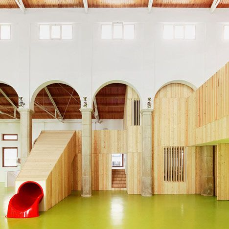 Spanish architects Miquel Mariné Núñez and César Rueda Boné transformed an abandoned market hall in Aragon into a children's centre with a slide connecting its floors