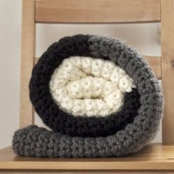 A great crochet project for beginners and pros alike. This chunky, soft, neutral colored blanket whips up in a flash and is a great gift!