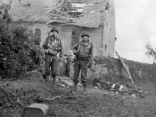 Shortly after the fighting at La Fière concluded, these American soldiers paused for a photographer with the heavily damaged manor house in the background. The bitter fighting at La Fière was a harbinger of combat to come in Normandy.