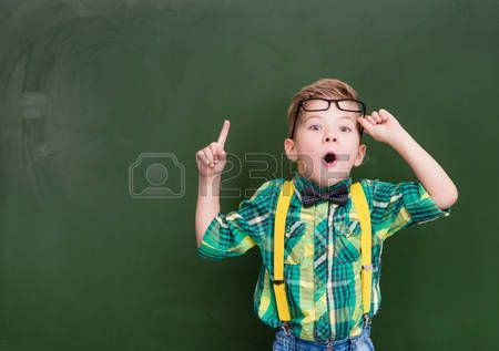 Surprised boy stands near empty chalkboard and showing finger up  Stock Photo