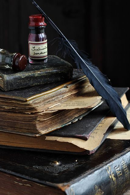 A stack of aged, world-worn antique books, a quill pen and a bottle of ink.