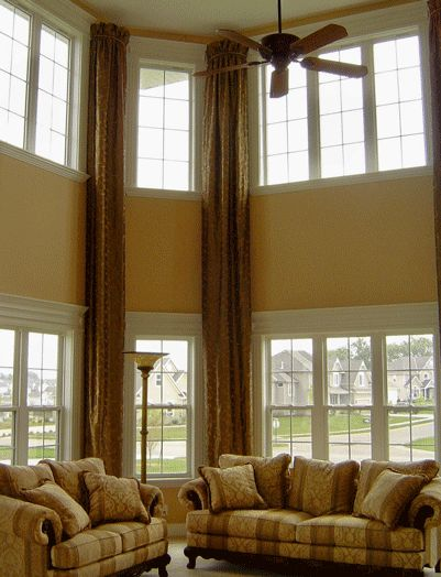 Long drapes accent the high ceiling family room for Window design 4 by 4
