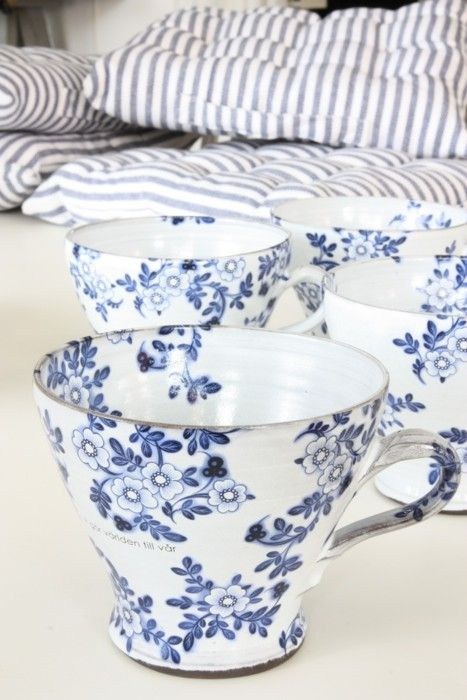 floral blue and white cups next to blue and white stripped cushions.