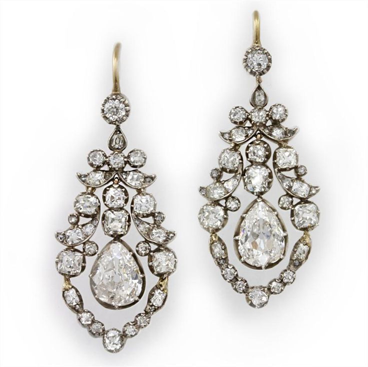 A pair of late Georgian open work diamond drop earrings, set with three graduating old brilliant-cut diamonds, the principle pear shaped diamond weighing approximately 3.50 carats the pair, suspended from two old brilliant-cut diamond within a diamond scroll design, all silver cut down collet to open yellow gold mounts with hook fittings, measuring approximately 4 cm in length, gross weight 8.5 grams, circa 1830.