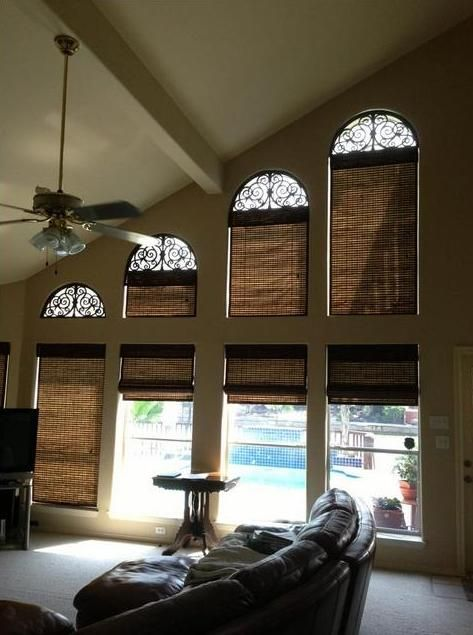 Budget Blinds of Corpus Christi creatively combined faux iron and woven wood shades for these high vaulted arched windows! Brilliant!