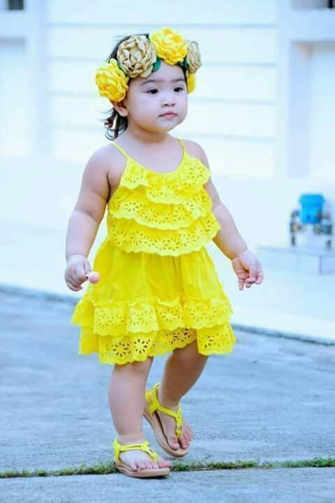 Adorable little girl in yellow dress and yellow flowered crown on her head