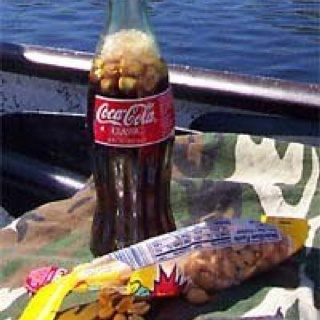 Putting peanuts in your Coke, it's a Southern thang. I remember sitting on the porch with my PaPa counting train cars and sipping coke with peanuts.  He would also pour coke in a glass, then shake in a dash of salt.