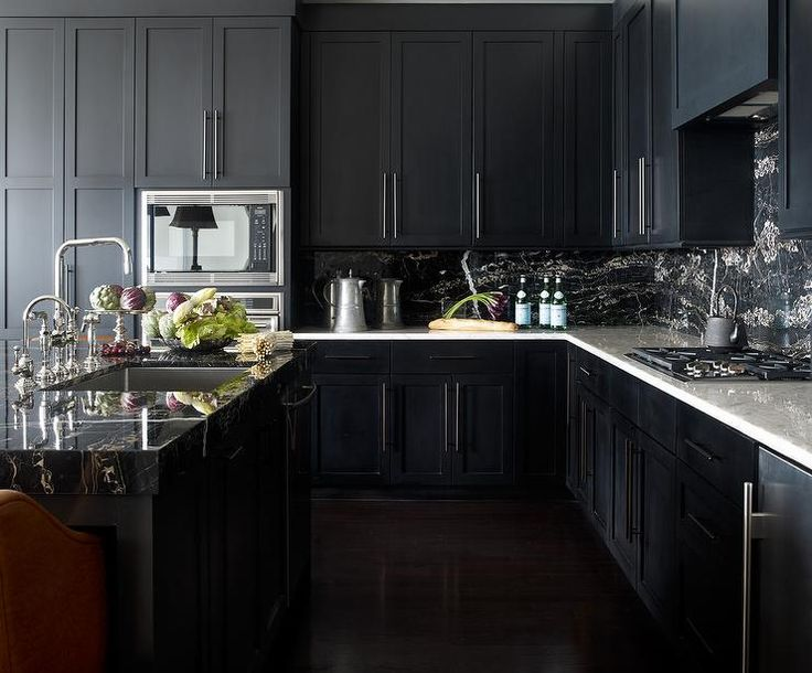 Amazing kitchen features noir cabinets paired with white marble countertops and a black marble backsplash.