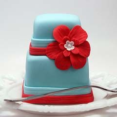 Retro two tier mini blue and red wedding cake embellished with a handmade red flower motif and red fondant strips.