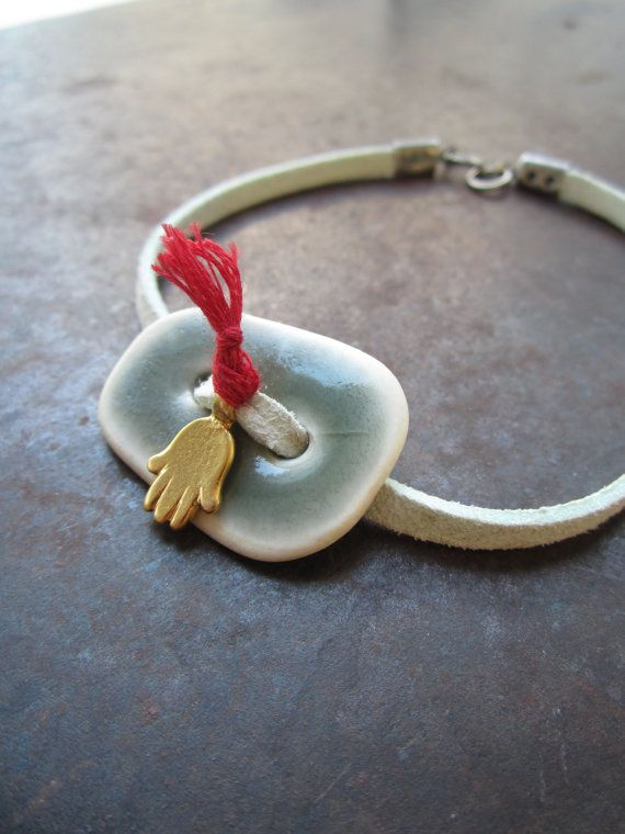 A bracelet made with soft sky blue leather and a hand made ceramic charm. A gold colour hamsa for good luck completes this unique design $24