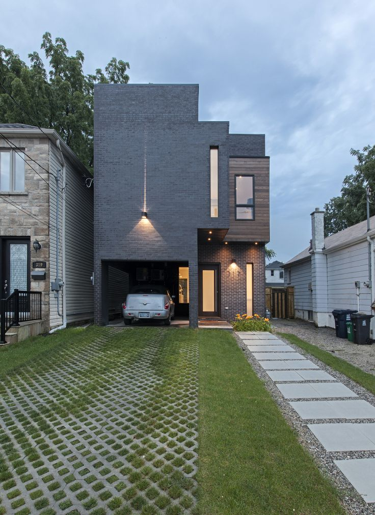 rzlbd > Totem House > The exterior of the house is a monolithic charcoal brick mass. Two small blocks on the north and south facade of this perfect mass have been extracted and cladded with wood.