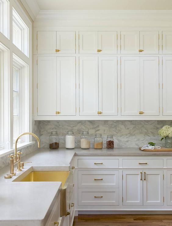 White stacked kitchen cabinets adorning vintage brass latch hardware are fixed above a marble backsplash lining white shaker cabinets topped with a gray quartzite countertop continuing around to a brass apron sink complemented with a brass gooseneck faucet positioned in front of a window.