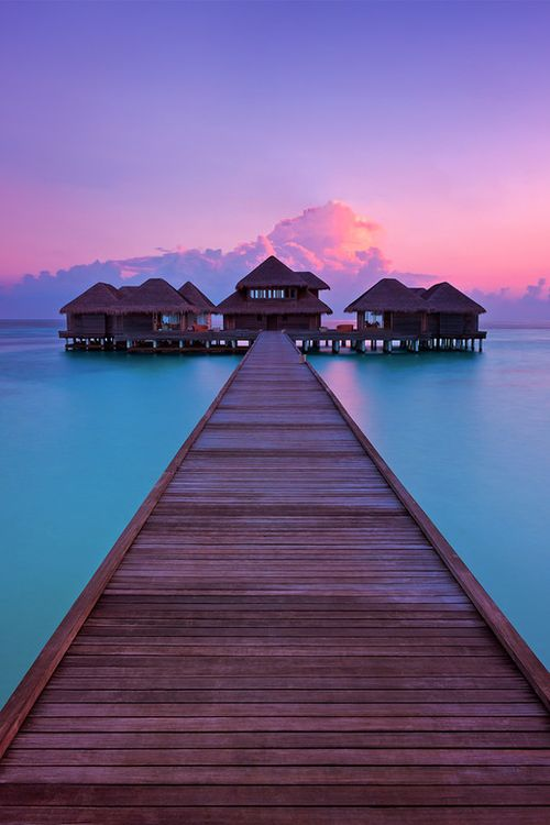 The moment just before sunrise, looking out at the crystal clear waters surrounding Huvafen Fushi's overwater spa in the Maldives, photo by Paul Reiffer.