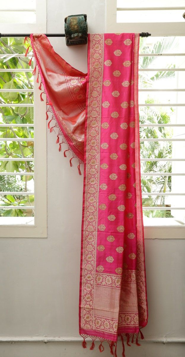 This exquisite dupatta is in Benares silk with a fuchsia pink base embellished with gold zari bhuttas and beige thread work. The border has gold zari and beige thread work, while the pallu has an i…