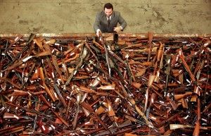 An Australian police detective adds another firearm to a pile of illegal rifles and shotguns. After the Port Arthur massacre, the government instituted a national buy-back program, ultimately paying around $527 million in exchange for Australians handing in nearly 700,000 weapons.(Reuters)